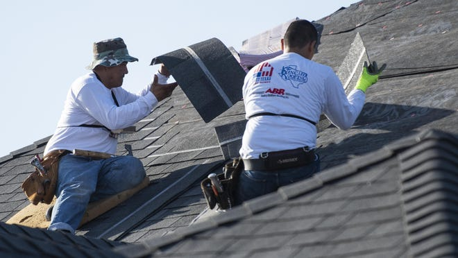 Roofers from Andrus Brothers Roofing install a roof on the future home of U.S. Marine Corp veteran Russell Snodgrass as a part of the Owens Corning National Roof Deployment Project on Monday in Lubbock.