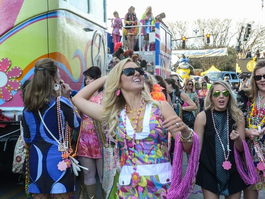 Members of the Krewe of Hip Huggers throw beads to the crowd during the 2016 Grand Mardi Gras Parade in downtown Pensacola. The parade returns Saturday.