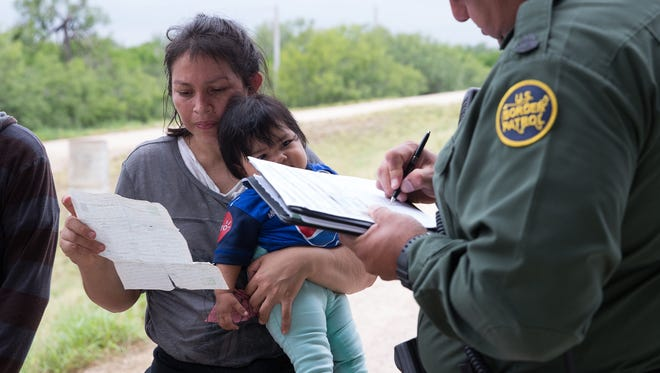 A U.S. Border Patrol agent talks to a migrant women who was found with a group of families from Honduras & Guatemala near McAllen, Texas.