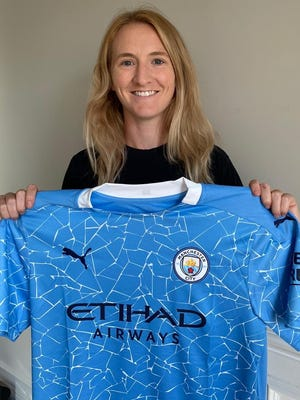Former Whitman-Hanson High star Sam Mewis holds up her new Manchester City jersey after signing with the English professional team. Photo courtesy of Manchester City