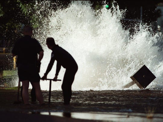 Salem police and firefighters try to cope with a broken water main along Liberty Street near Mill Street SE in 2000.