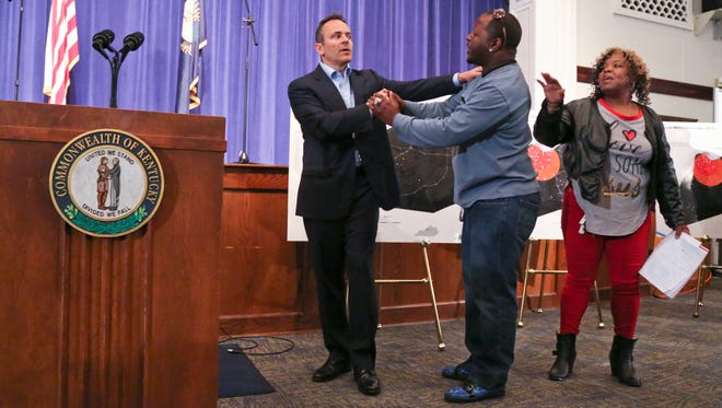 Gov. Matt Bevin shakes audience member Kalvin Brown's hand after the Louisville resident approached the podium during the Kentucky governor's talk about curbing the violence through prayer. Brown said more money was needed as well to provide jobs and start businesses through loans.