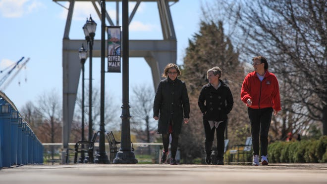 Chris Greenfield, left, Dawn Benson and Michele Ashley walk down the Riverfront in Wilmington during their lunch break Tuesday.