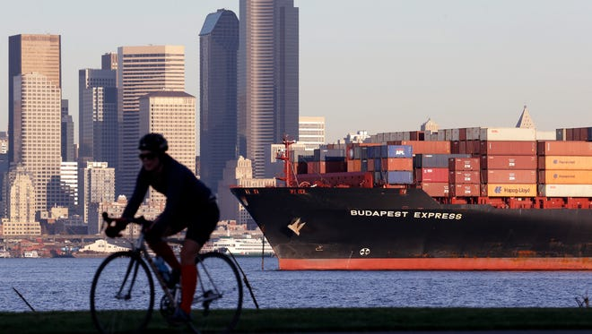 A bicyclist rides in view of a loaded container ship anchored in Elliott Bay near downtown Seattle. The Commerce Department releases international trade data for February on Thursday, April 2, 2015. (AP Photo/Elaine Thompson, File)