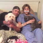 Bart and Jill Conley lay on their bed at home with their pets, Jill tethered to an oxygen machine.