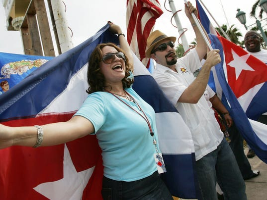 Cubans wave Cuban and US flags as they c