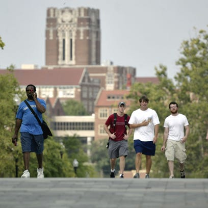 FILE - Students walk across campus at the University