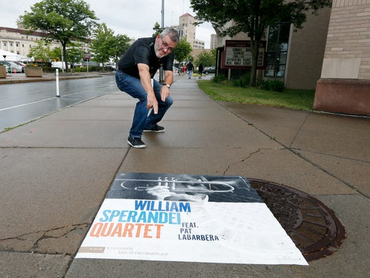John Nugent, producer and artistic director of the Xerox Rochester International Jazz Festival, has some fun on his way to one of the venues in this file photo. Temporary advertisements on sidewalks, also using washable paint, would be allowed under Mayor Lovely Warren's proposal during special events, large conferences and other such gatherings.