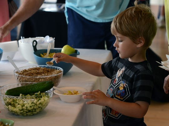 Oliver Sallis, 5, makes some chicken salad for the kids chicken salad competition Sunday during the Junior League of Pensacola's third annual Dish It Out, at the Corrine Jones Community Center. The event is a tasting and shopping showcase for people who love to eat, cook and entertain.