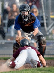 Irondequoit catcher Jackson DeJohn prepares to tag Pittsford Mendon's Kyle Wallman out at home plate during a regular season game at Irondequoit High School on Wednesday, May 16, 2018.