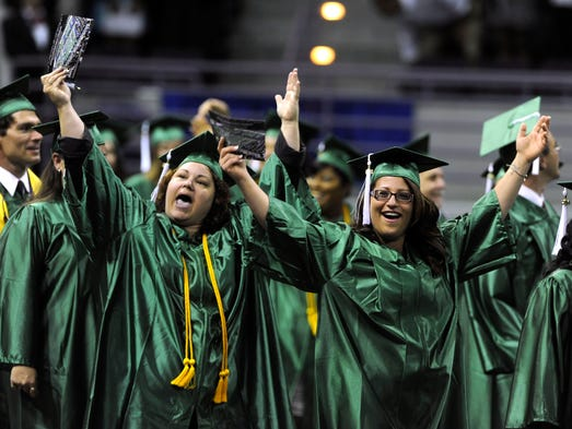 Cynthia Licharowicz and Angela Camuto make a grand entrance Sunday during the Pensacola State CollegeCommencement at the Pensacola Bay Center.