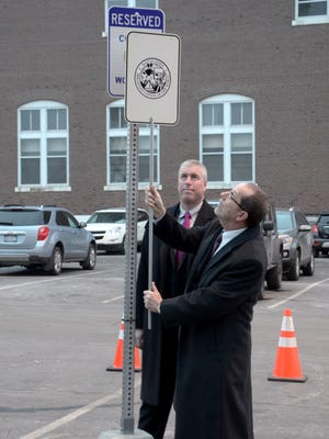 Battle Creek Mayor Dave Walters removes the cover of the newly installed parking sign for wounded military veterans at City Hall. Behind Walters is Timothy Hutson, first vice president at Hilliard Lyons in Battle Creek. The financial consulting firm, which also employs Walters, is paying for the signs.
