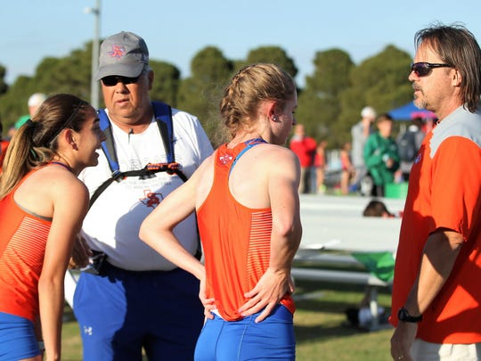 Central High School's Bailey Kinney, far left, and fellow senior Olivia Dabbert, middle, talk things over with Central head coach Bobby Ventura and cross country coach Keith Meek, right, at the Cotton Patch Relays on March 29, 2018, in Wall.