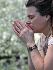 Jenny Powell of Mansfield prays during the National Day of Prayer service on the square in downtown Mansfield Thursday.