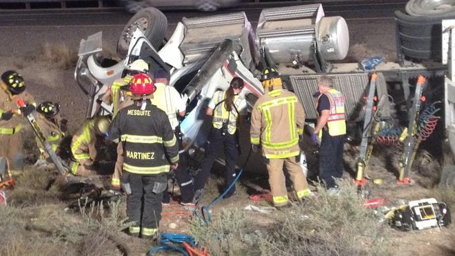 Emergency responders work to free a Las Vegas driver from the wreckage of his semi cab early Wednesday morning three miles northeast of the Nevada-Arizona state line on Interstate 15. Gail and Arlene Lettau were seriously injured in the crash, which is attributed to Gail allegedly falling asleep at the wheel, Arizona Highway Patrol Sgt. John Bottoms said.