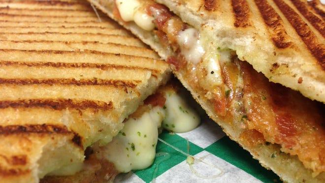 The BPT sandwich is made with bacon, pesto, tomato, mozzarella, and cilantro aioli on grilled sourdough.