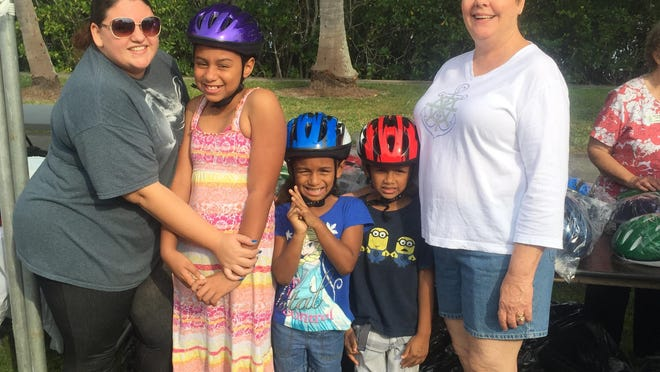 The Pilot Club of Fort Myers distributed 300 bicycle helmets during the recent Reading Festival in Centennial Park. Among the recipients were Victoria Morgan (second from the left), Mercury Morgan, and Isabella Morgan. Pictured with them are their mother, Luz Santana, and Pilot Club President Patsy Tortora.