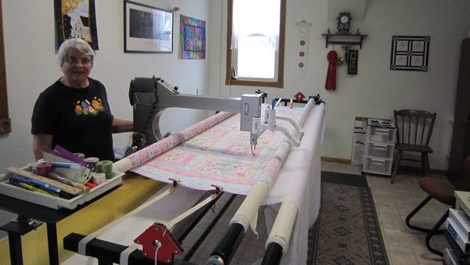 Lois Warnert stands next to her long-arm quilting machine in the repurposed jail.