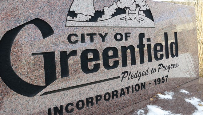 """The city of Greenfield's slogan, """"Pledged to Progress,"""" is prominently displayed in many locations around the community, including this bench near the Greenfield Public Library."""