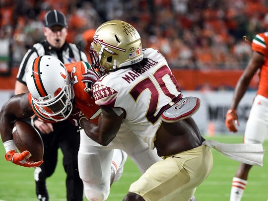 Miami Hurricanes tight end Christopher Herndon IV is tackled by Florida State Seminoles defensive back Trey Marshall during the first half of Saturday's game.