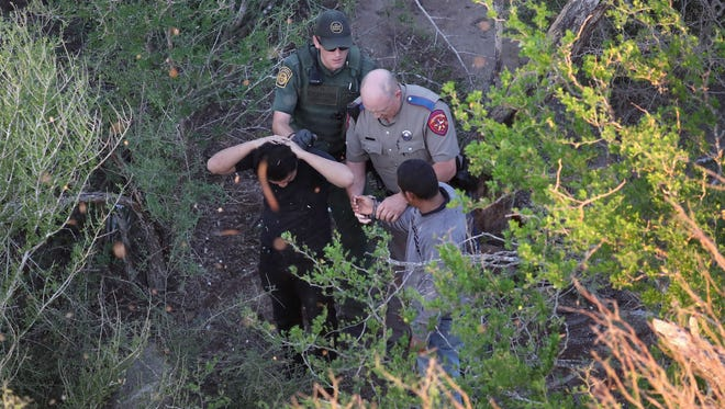 A Texas state trooper and a U.S. Border Patrol agent detain undocumented immigrants near McAllen, Texas.