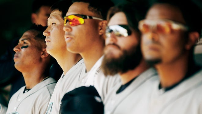 Seattle Mariners first baseman Dae Ho Lee, second from left, looks on from the dugout during the seventh inning of a baseball game against the Texas Rangers, Monday, April 4, 2016, in Arlington, Texas. Lee made his MLB debut after playing professionally for 15 years in Korea and Japan. Texas won 3-2.