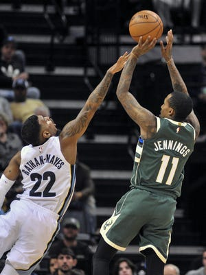 Bucks guard Brandon Jennings hoists a shot over the outstretched arm of Grizzlies guard Xavier Rathan-Mayes during the second half on Monday night.