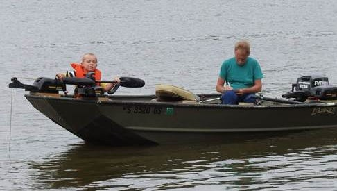 Carter Tulachka and volunteer boat Captain Ron Beatty recording Carter's first-place winning bluegill during Hooked on a Hobby Kids' Fish Derby June 16.