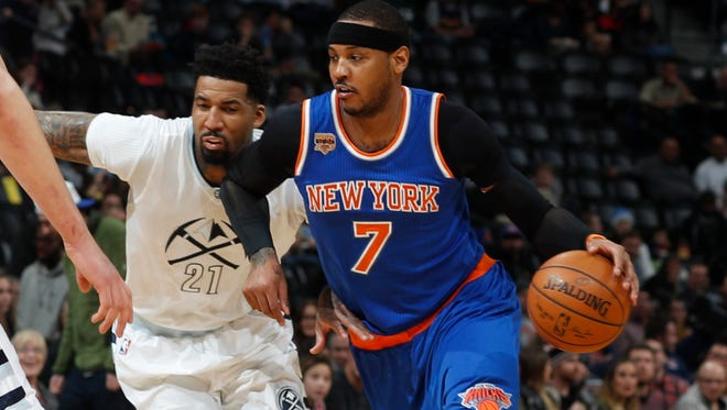 Knicks forward Carmelo Anthony, right, drives to the basket past Denver Nuggets forward Wilson Chandler in the first half of an NBA basketball game Saturday, Dec. 17, 2016, in Denver.