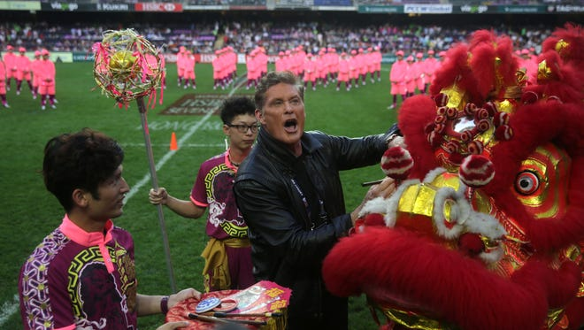 David Hasselhoff (C) paints the head of a Chiense Dragon to bring good luck during the opening ceremony of the rugby sevens tournament in Hong Kong on April 8, 2016.