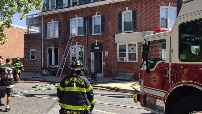 Firefighters stand outside a residence on the 1200 block of Linden Street where a fire was reported.