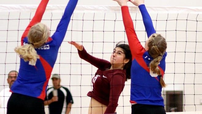 Junior Lady Cat Jolene Perez (15) tried to split the Las Cruces High block during Saturday's non-district volleyball match with the visiting Bulldawgs.