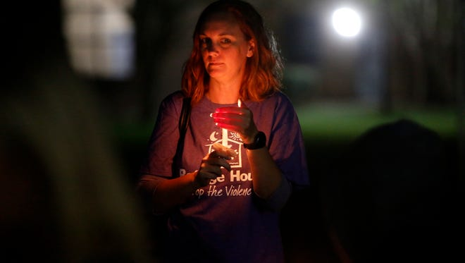 Attendees light candles in memory of those who lost their lives to domestic violence at the annual Domestic Violence Awareness Month Candlelight Vigil and Survivor Speak-Out held Oct 18 at TCC's Workforce Development Center.