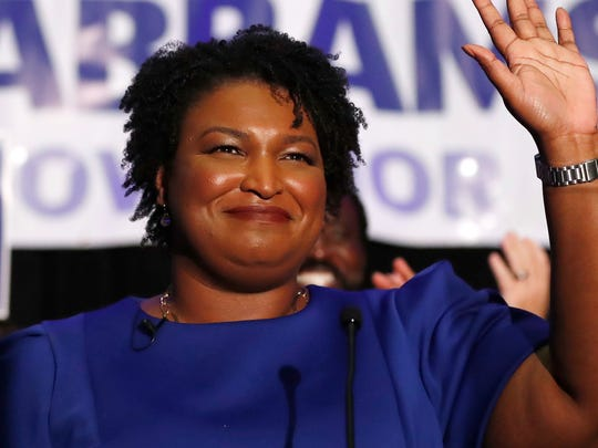 Stacey Abrams waves to supporters after speaking at an election night watch party in Atlanta.