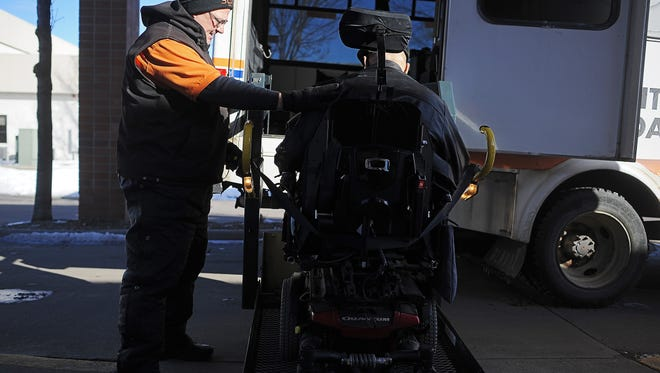 Ray Ellefson, a Sioux Area Metro Paratransit operator, helps passenger Jim Hembree, of Sioux Falls, onto the bus Monday, Feb. 8, 2016, outside Active Generations in Sioux Falls.