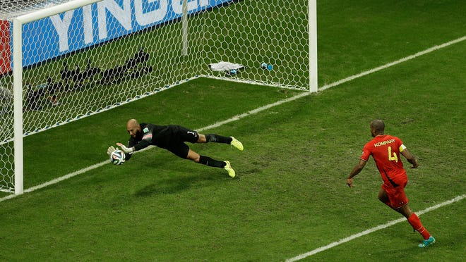United States' goalkeeper Tim Howard makes a save as Belgium's Vincent Kompany, right, looks on during the World Cup round of 16 soccer match between Belgium and the U.S. on Tuesday in Brazil.