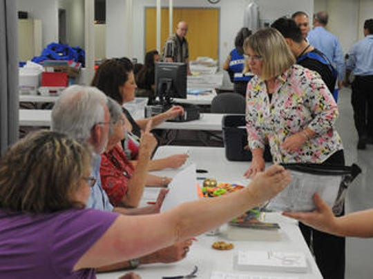 Washoe County registrar of voters Luanne Cutler, center right, oversees the ballot receiving line Tuesday evening at the Washoe County complex.