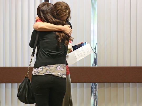 Family members of Robert Pape hug outside the courtroom at the Larson Justice Center on Friday, October 3, 2014, after the Riverside County District Attorney's office dropped charges against Pape and Christin Smith for the 2006 triple slaying in Pinyon Pines.