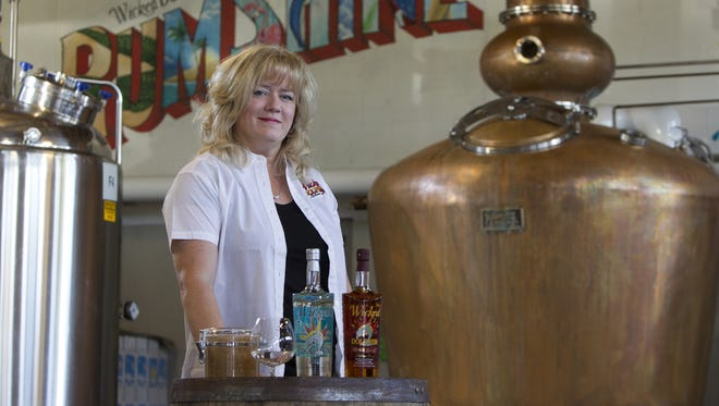 Owner JoAnn Elardo near the still at the Wicked Dolphin Rum Distillery in Cape Coral.