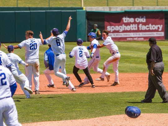 Dixie's baseball team runs onto the field to celebrate with Cooper Vest (7) after he hit a walk-off home run to win the 3A state championship, Saturday, May 20, 2017.