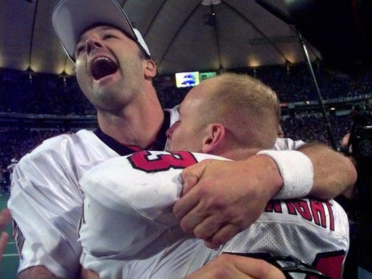 Chris Chandler, quarterback for Atlanta (left) celebrates an NFC Championship win in 1999.