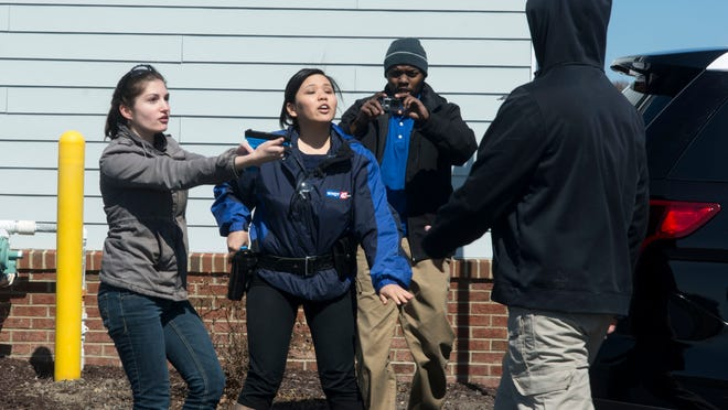 Journalist Maria Counts aims a gun at a faux attacker with a knife during an exercise.