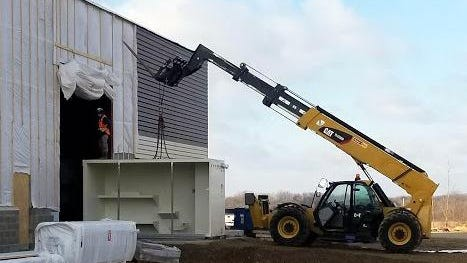 A modular jail cell is moved Monday into the completed outer new county jail building. These will be welded together to create 220 bed cell blocks.