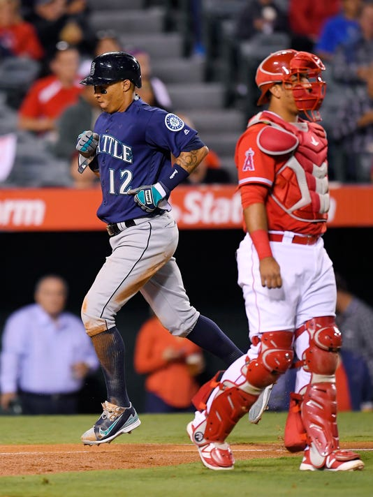Seattle Mariners' Leonys Martin, left, scores on a sacrifice fly hit by Ketel Marte as Los Angeles Angels catcher Carlos Perez walks toward the mound during the second inning of a baseball game, Tuesday, Sept. 13, 2016, in Anaheim, Calif. (AP Photo/Mark J. Terrill)