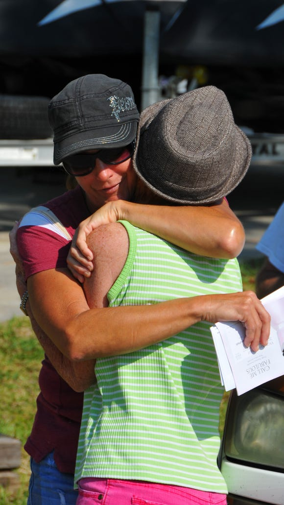 Neighbors Kathleen Cano and Patti Knobloch embrace near the scene of a fatal stabbing of children in Palm Bay.  Knobloch had just given stuffed animals to put by the mailbox.