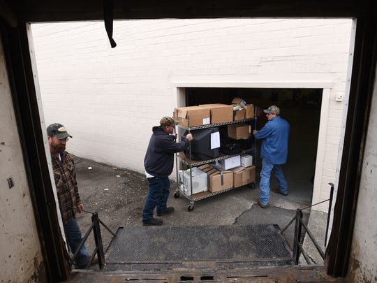 Muskingum County maintenance department workers Rob Frame, left, Scott Lee and Jeff Butler move items from the Board of Elections in the Board's new building on Market Street in Zanesville on Monday.