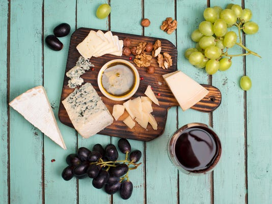 Grapes, red wine, cheeses, honey and nuts over shabby wood.