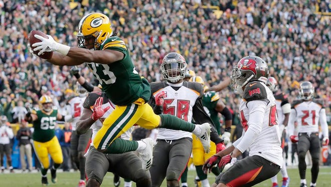 Green Bay Packers running back Aaron Jones (33) dives into the end zone to score the game-winning touchdown against the Tampa Bay Buccaneers in overtime at Lambeau Field on Sunday, December 3, 2017 in Green Bay, Wis.