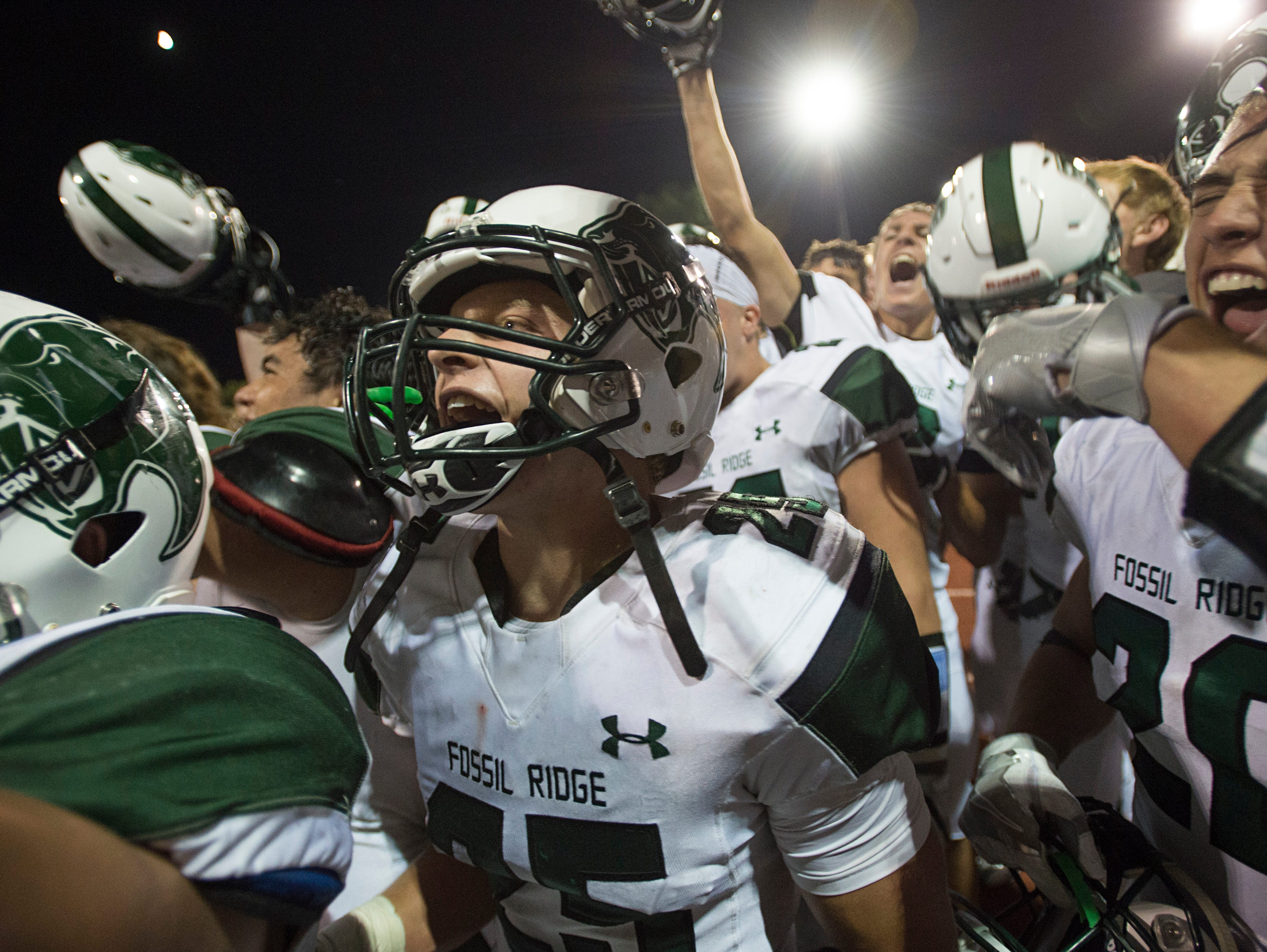 Fossil Ridge celebrates a 21-17 victory over Rocky Mountain High School at French Field Thursday.