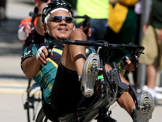 Wayne State University president M. Roy Wilson on a recumbent bike crosses the finish line after doing 100 miles during the inaugural Baroudeur which finished at Gullen Mall on the campus of Wayne State in Detroit on Saturday, August 21, 2015.